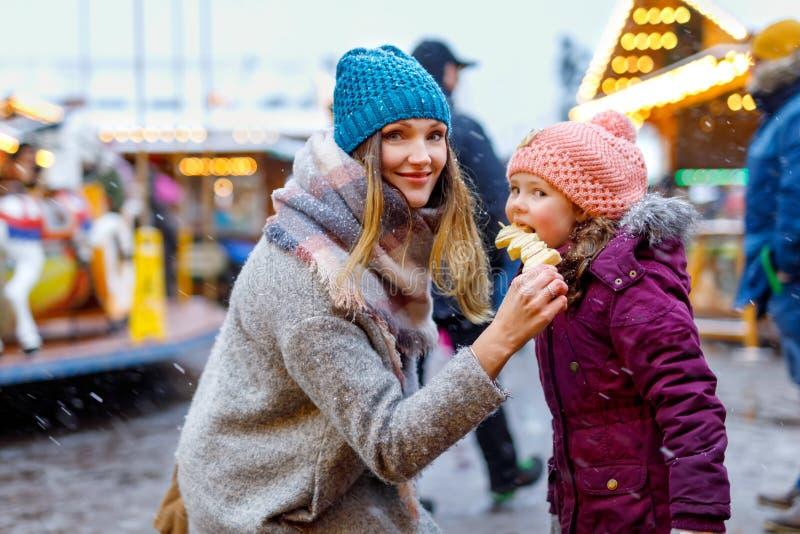 Barnet fostrar, och dottern som äter täckt vit choklad, bär frukt på steknålen på traditionell tysk julmarknad arkivfoto