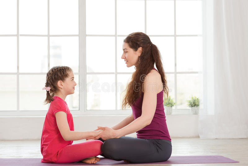 Barnet fostrar och dottern som gör yogaövning royaltyfri fotografi