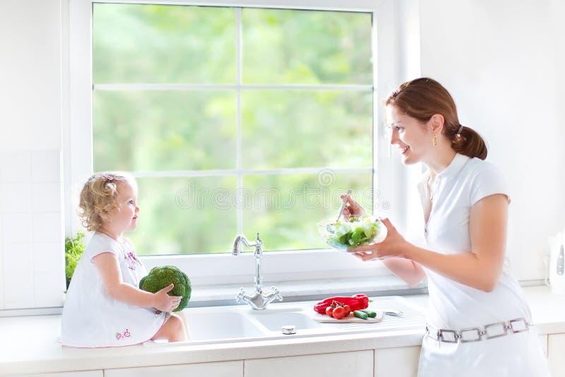 Barnet fostrar och hennes gulliga litet barndottermatlagning royaltyfri fotografi