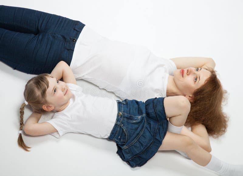 Barnet fostrar och hennes le lilla dotter som ligger på golvet arkivfoton