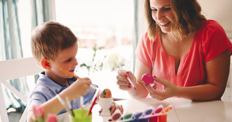 Barnet fostrar och hennes son som har gyckel, medan måla ägg för påsk royaltyfri foto