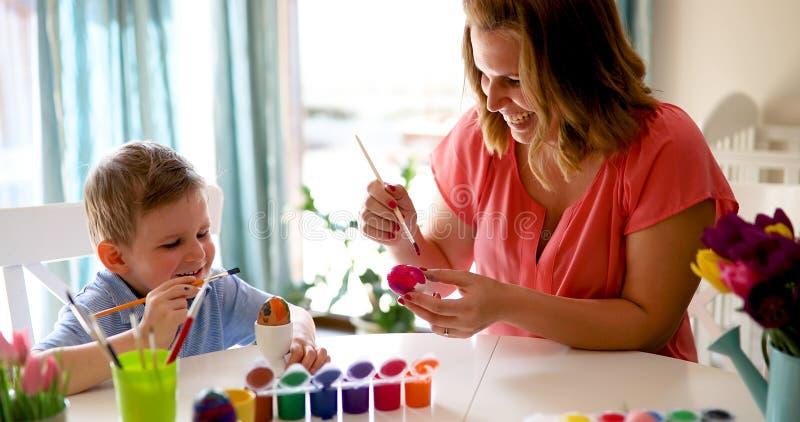 Barnet fostrar och hennes son som har gyckel, medan måla ägg för påsk royaltyfria foton