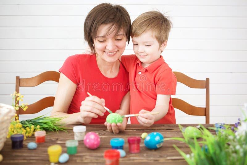 Barnet fostrar och hennes son som har gyckel, medan måla ägg för påsk Lyckliga easter för familjmamma- och barnsonmålarfärg ägg m arkivbild