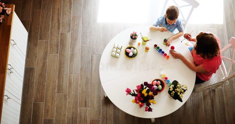 Barnet fostrar och hennes son som har gyckel, medan m?la ?gg f?r p?sk fotografering för bildbyråer