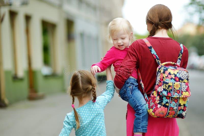 Barnet fostrar och hennes två gulliga döttrar utomhus royaltyfri bild