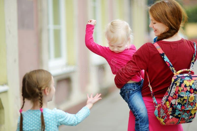 Barnet fostrar och hennes två gulliga döttrar utomhus fotografering för bildbyråer