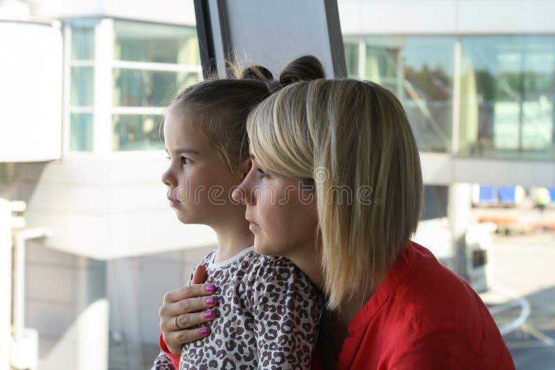 Barnet fostrar och hennes väntande flygplan för dottern i flygplats royaltyfri fotografi