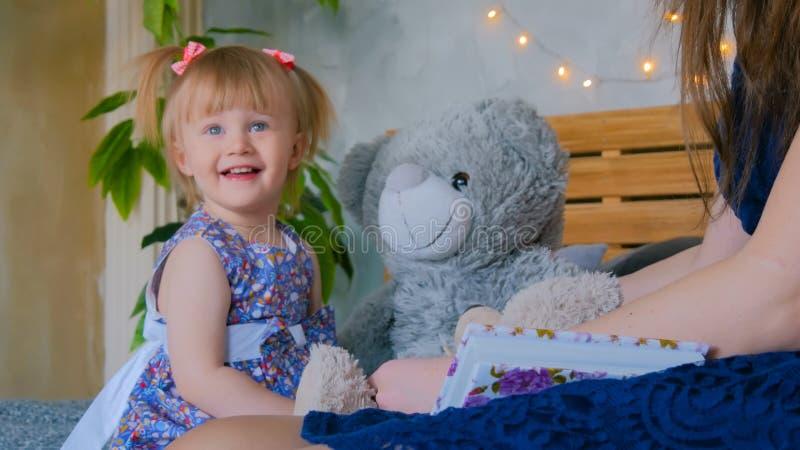 Barnet fostrar, och hon behandla som ett barn dottern som hemma spelar togerher fotografering för bildbyråer