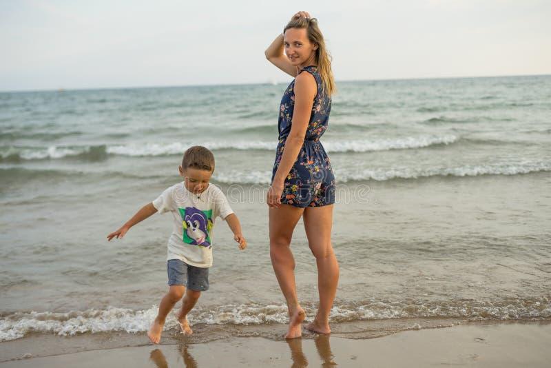 Barnet fostrar, och le behandla som ett barn pojkesonen som spelar på stranden på solnedgången Positiva mänskliga sinnesrörelser, arkivfoto
