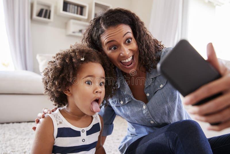Barnet fostrar och litet barndottern som hemma tar selfie royaltyfria foton