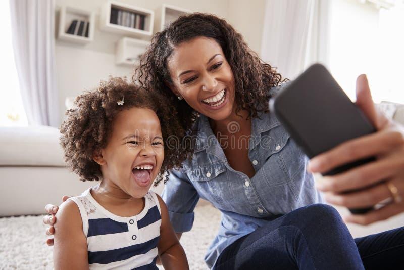 Barnet fostrar och litet barndottern som hemma tar selfie royaltyfria bilder