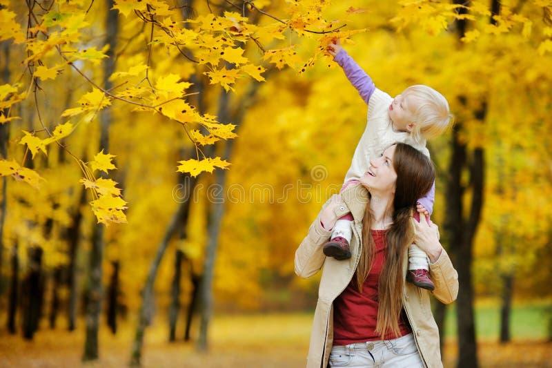 Barnet fostrar, och litet barnflickan har gyckel på hösten royaltyfri bild