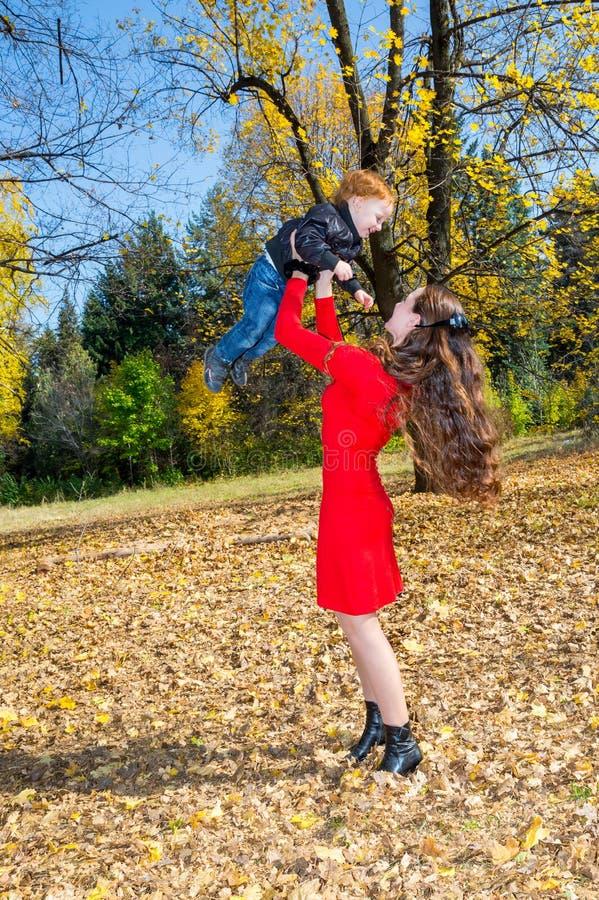 Barnet fostrar, och sonen i höst parkerar lycklig familj: keln för moder- och barnpojkelek på höst går i natur utomhus arkivfoto