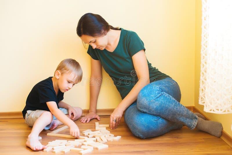 Barnet fostrar och sonen som spelar med inomhus träkvarter Den lyckliga familjen spenderar tid tillsammans hemma arkivfoto