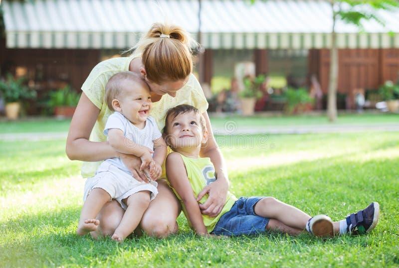Barnet fostrar och två söner som tycker om härlig dag arkivbild