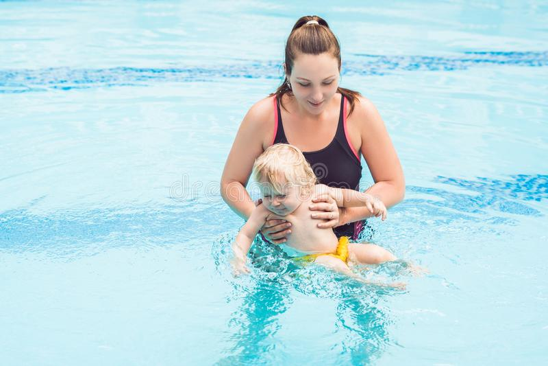 Barnet fostrar undervisar hennes lilla son, hur man simmar i en simbassäng royaltyfri fotografi