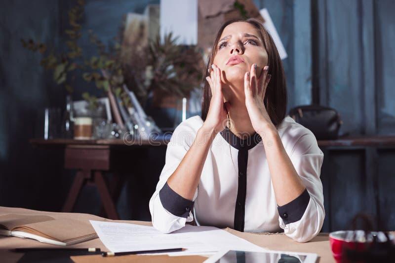Barnet frustrerade kvinnan som framme arbetar på kontorsskrivbordet av bärbara datorn arkivbild
