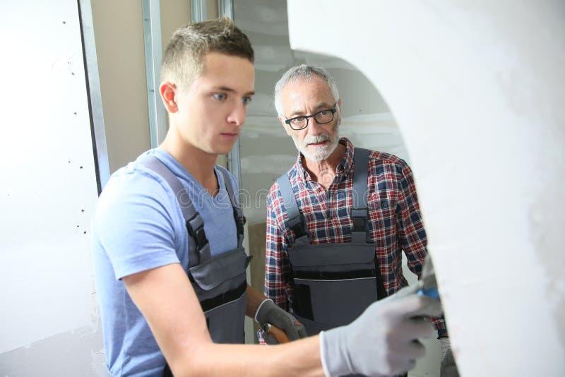 Barnet gå i lära med den plastery instruktören som arbetar väggen arkivfoto