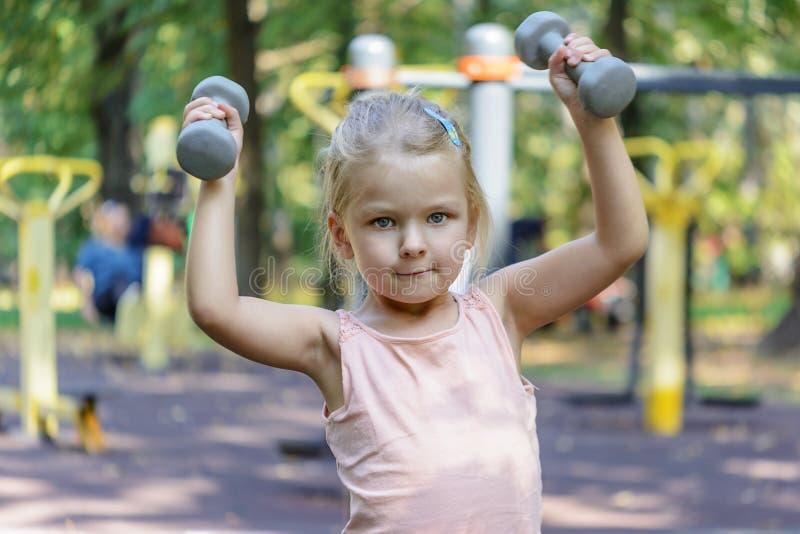 Barnet gör övningar, med hantlar Lite flicka med blont hår royaltyfri fotografi