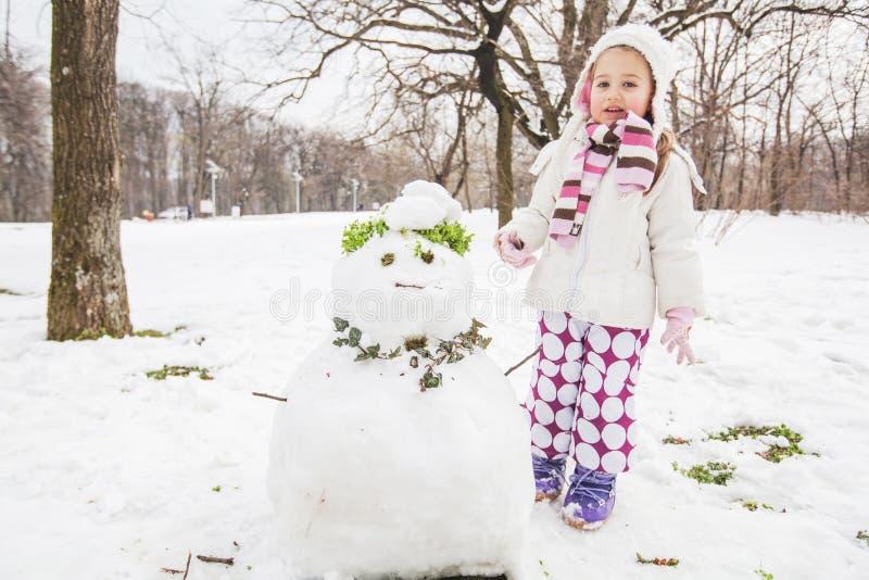 Barnet gör en snögubbe i parkerar på vinterdagen arkivbilder