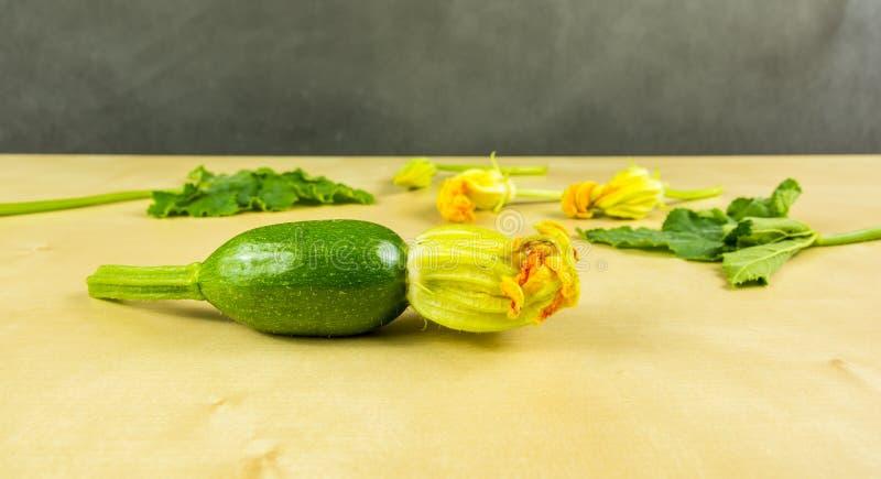 Barnet gör grön zucchinin med blomman I bakgrunden, blommorna och sidorna arkivbild