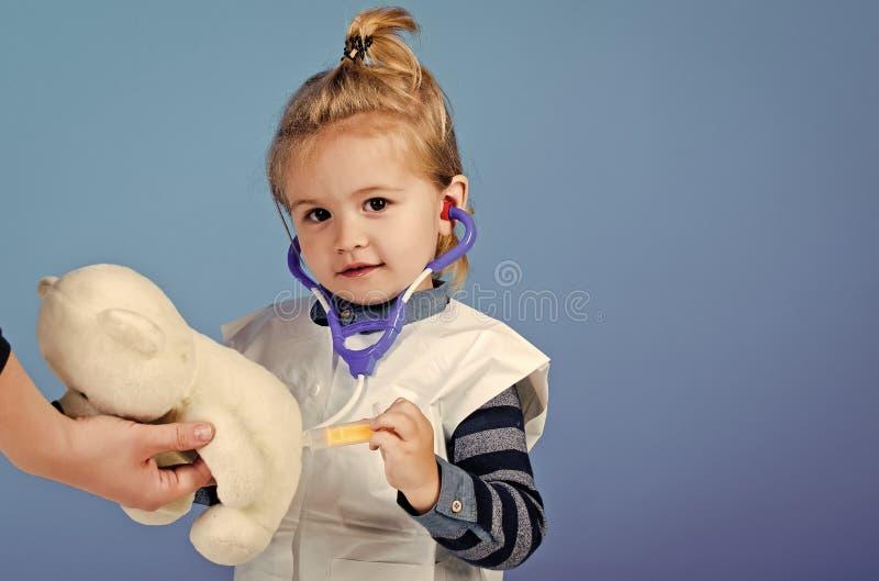 Barnet gör injektionen till nallebjörnen i mödrar räcker royaltyfria bilder