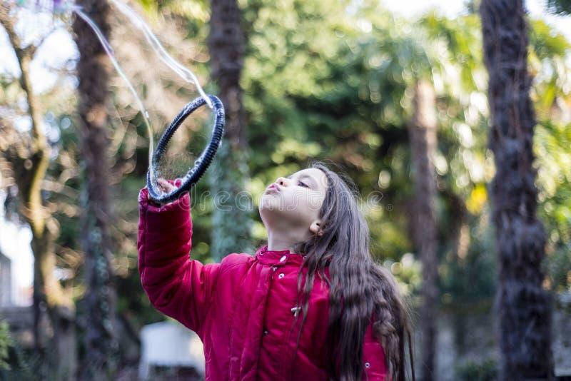 Barnet gör jätte- såpbubblor arkivbilder