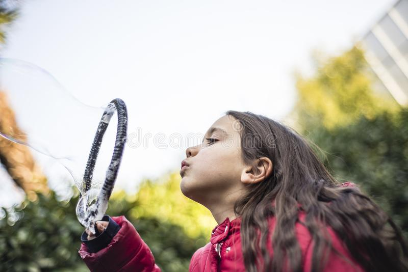 Barnet gör jätte- såpbubblor arkivbild