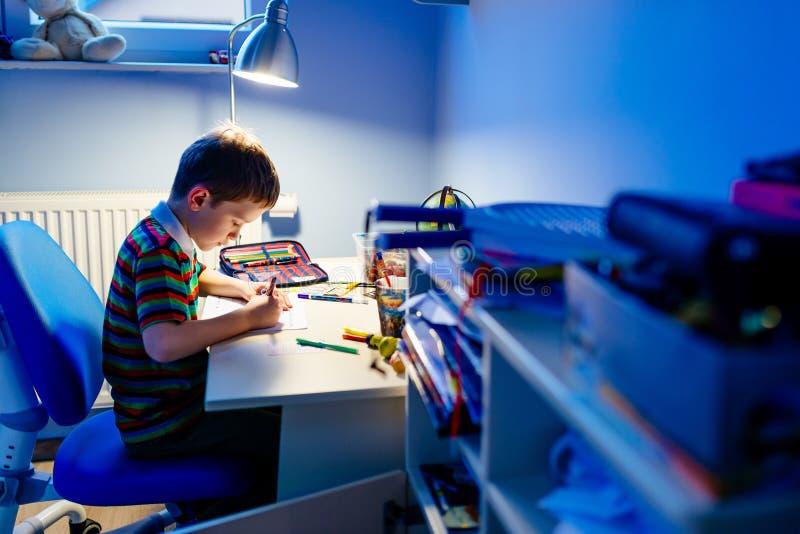 Barnet gör läxa i ljuset av lampan arkivfoton
