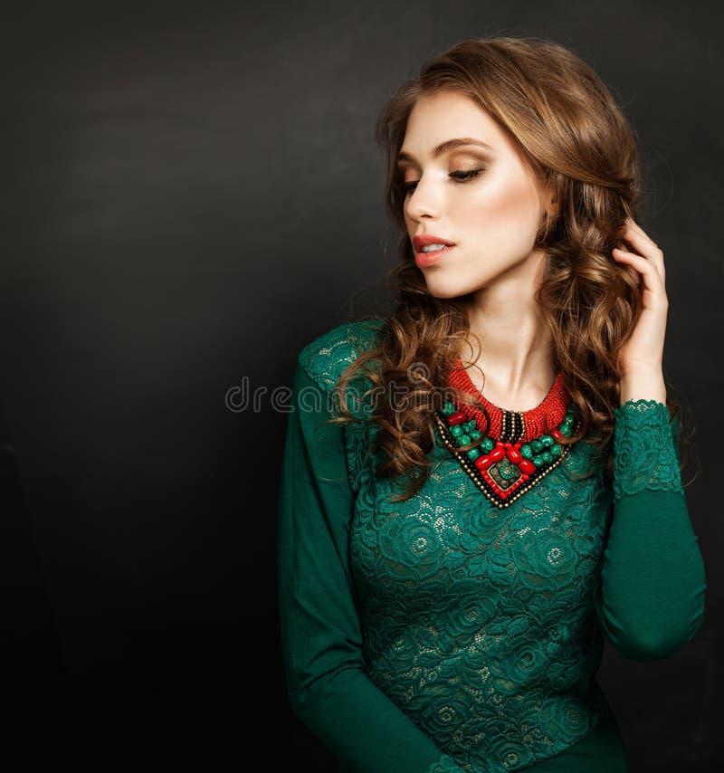 Barnet gör perfekt kvinnan som bär den gröna klänningen och halsbandet för röda koraller royaltyfri fotografi