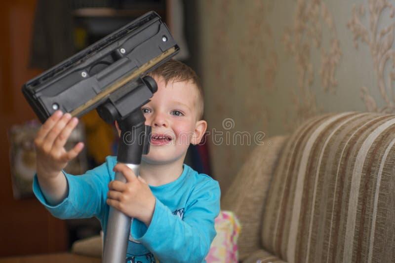 Barnet gör ren huset med en dammsugare arkivfoto