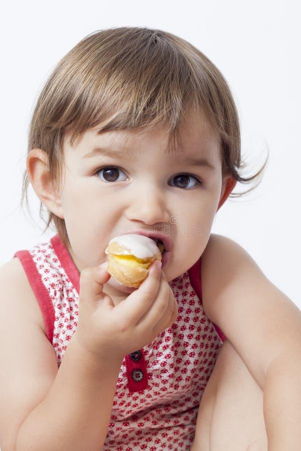 Barnet 2 gamla år behandla som ett barn äta bakelse med nöje royaltyfri bild
