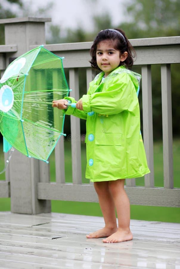 barnet gears henne regn royaltyfri bild