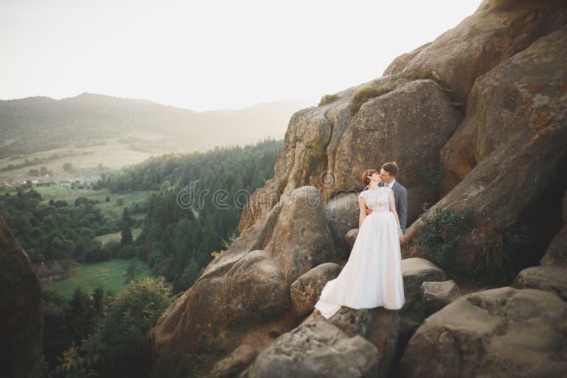 Barnet gifta sig nyligen par, bruden och brudgummen som kysser och att krama på perfekt sikt av berg, blå himmel royaltyfri bild