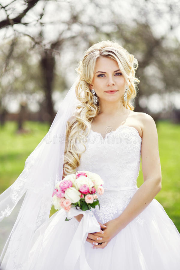 Barnet härlig brud med en bukett, är våren, äppleorch royaltyfri fotografi