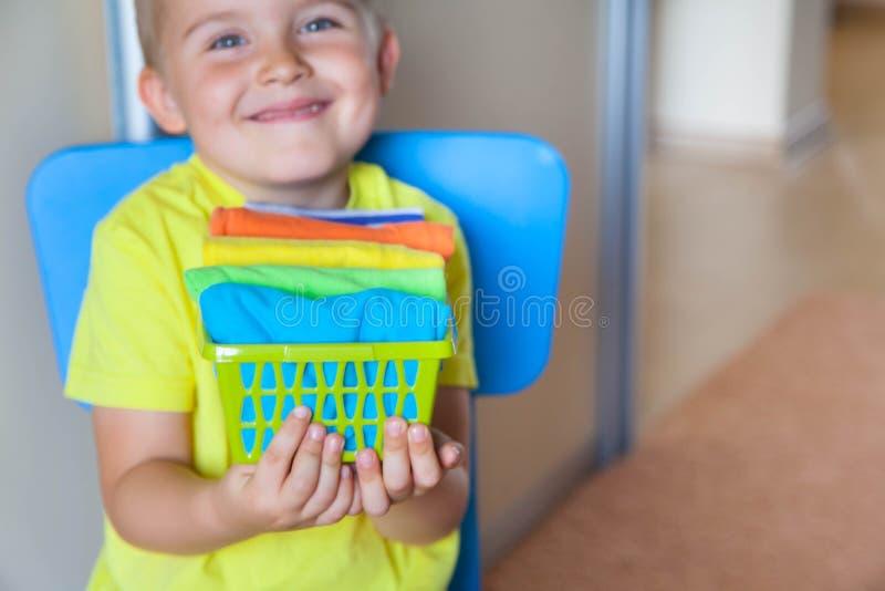 Barnet håller hans saker Pojken sätter T-tröja i en drawe royaltyfria bilder