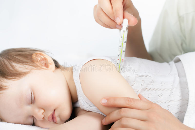 Barnet har en hög temperatur eller en feber, genom att använda en termometer royaltyfri foto