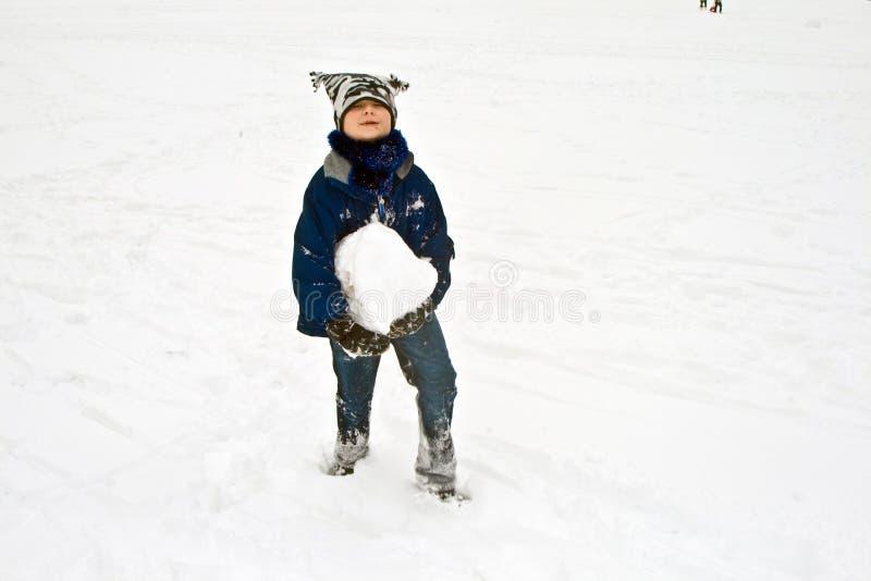 Barnet har ett stort att kasta snöboll för royaltyfri bild