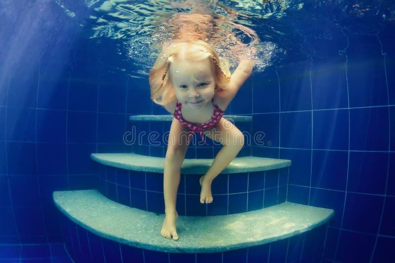 Barnet hoppar undervattens- in i simbassäng fotografering för bildbyråer