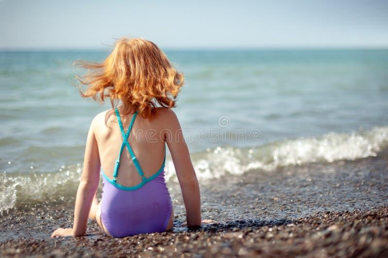 Barnet i en baddräkt sitter på stranden och drömmarna fotografering för bildbyråer