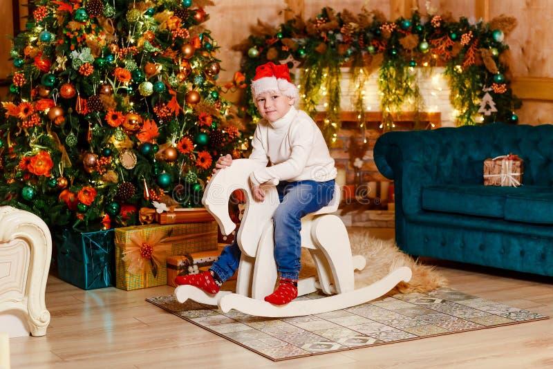 Barnet i en röda Santa Hat sitter på en trähäst för jul royaltyfri bild