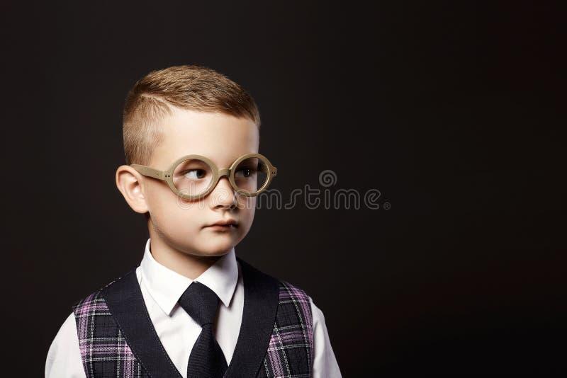Barnet i exponeringsglas nära skolar skrivbordet royaltyfri foto
