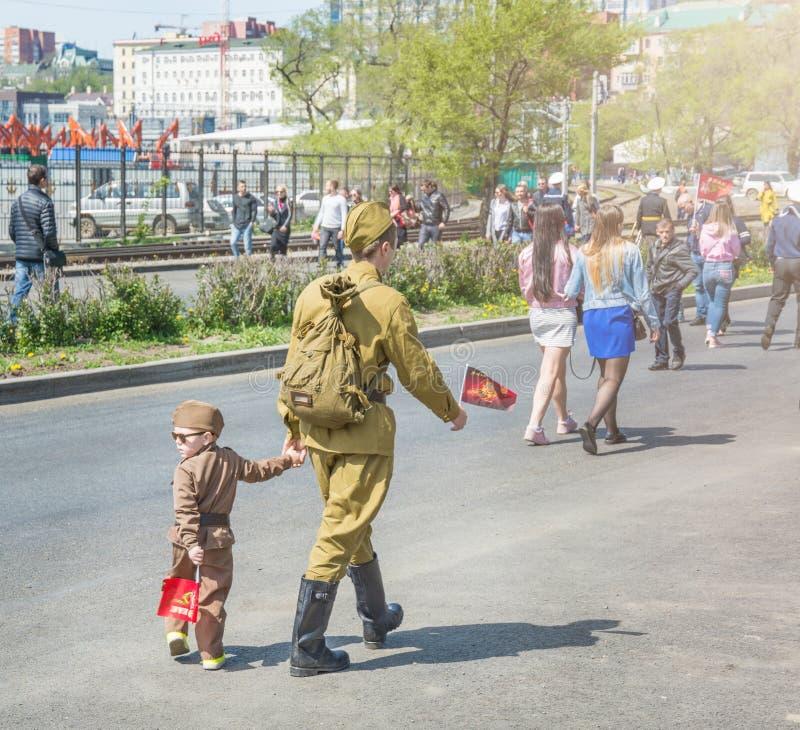 Barnet i form av militär ståtar, med föräldrar beröm av segerdagen ståtar på Maj 9 russia vladivostok royaltyfria bilder