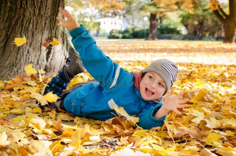 Barnet i höst eller nedgången parkerar att spela med sidor royaltyfri fotografi