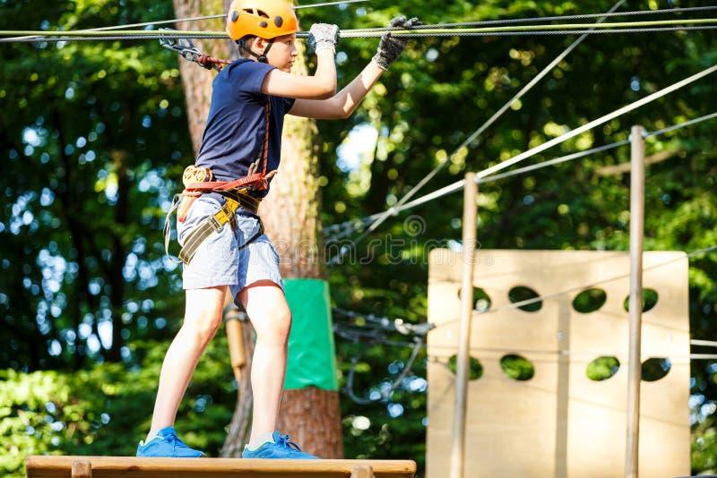 Barnet i skogaffärsföretag parkerar Ungen i orange hjälm och blå t-skjorta klättrar på hög repslinga Expertis och klättra för vig arkivfoto