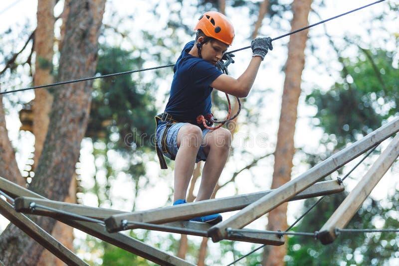 Barnet i skogaffärsföretag parkerar Ungen i orange hjälm och blå t-skjorta klättrar på hög repslinga Expertis och klättra för vig royaltyfri fotografi