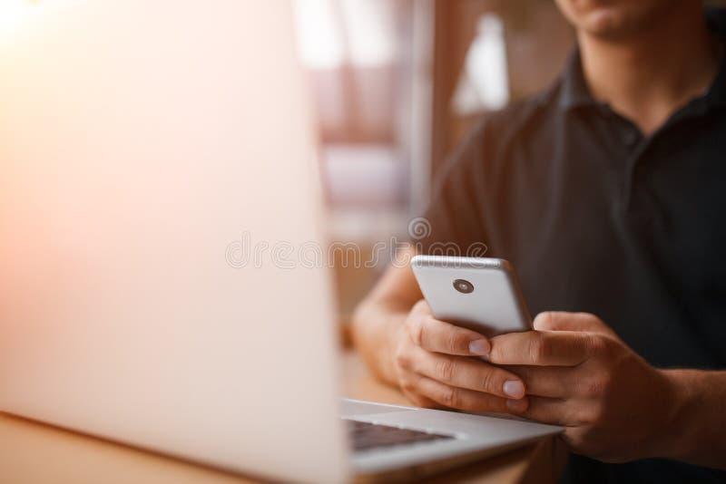 Barnet ilar mannen som arbetar med bärbar datordatoren och smartphonen royaltyfri fotografi
