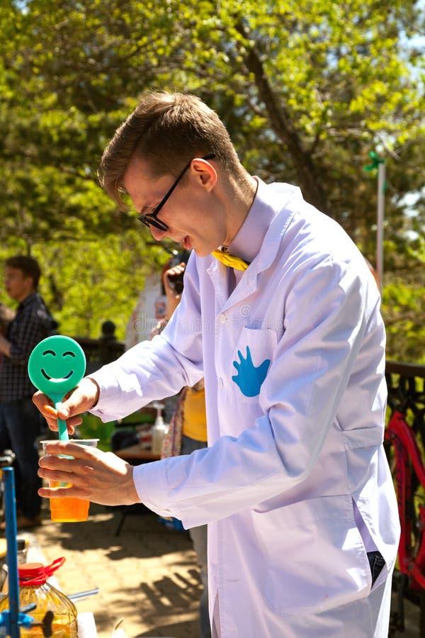 Barnet ilar professorn som ut bär ett experiment på vetenskapsshowen för ungar arkivfoto