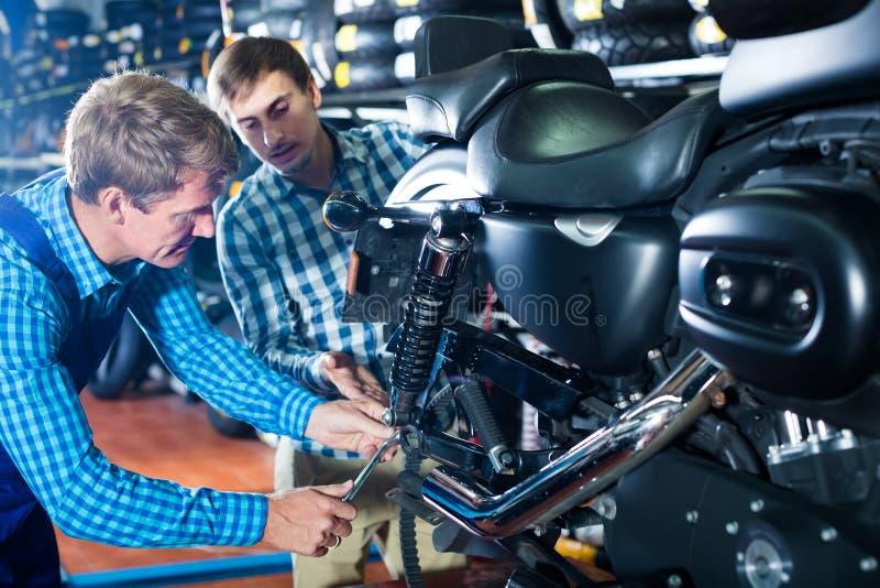 Barnet intresserade mankunden som frågar teknikeren om motorcykeln fotografering för bildbyråer
