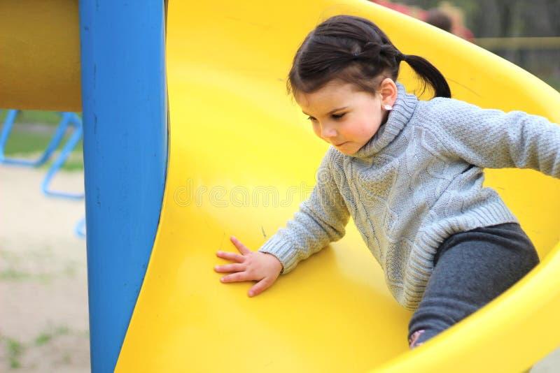 barnet kör av en brant glidbana på lekplatsen arkivbilder